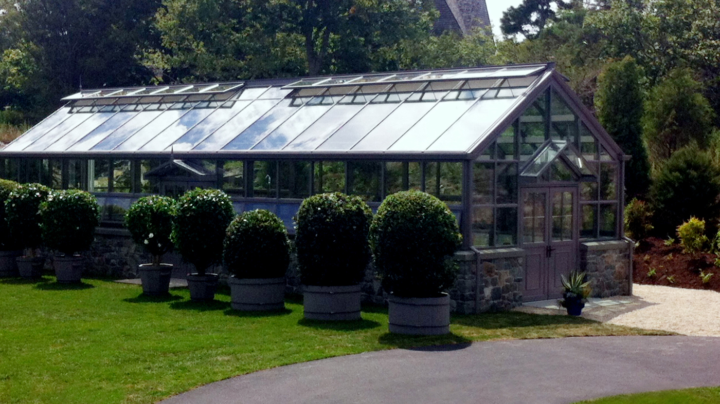 This straight eave, double pitch greenhouse with two gable ends includes two canopies and multiple accessories. Some of these accessories include aluminum base panels, bulbous trim, extruded gutter, round downspouts, ridge cresting, and multiple finials. The structure also features a custom