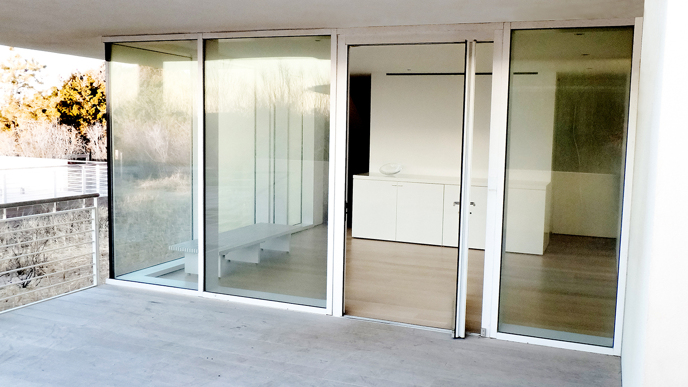 Complete Glazing Package features multiple curtain wall systems, a in-swing terrace door, and multiple sliding glass door systems.