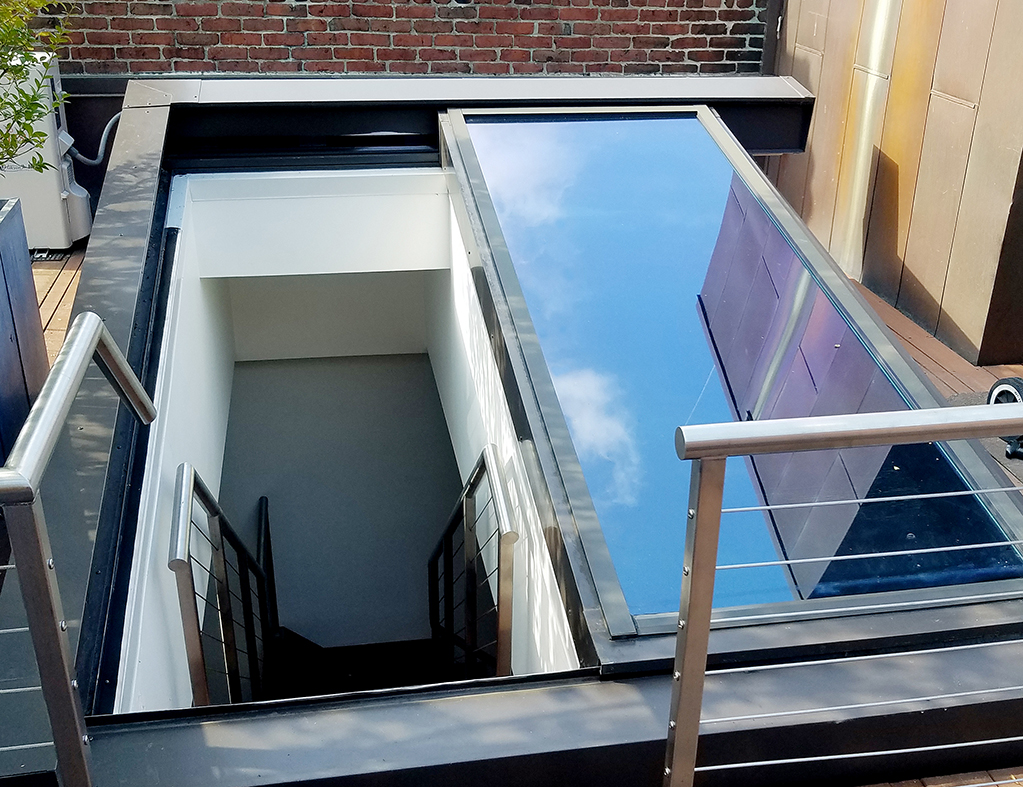 Skylight custom designed to a single slope retractable provided natural ventilation for a residence in an urban neighborhood with limited options.. The weather sensor recognizes wind speed and rain, triggering the motorized operator to automatically close the skylight when the conditions are no longer optimal.