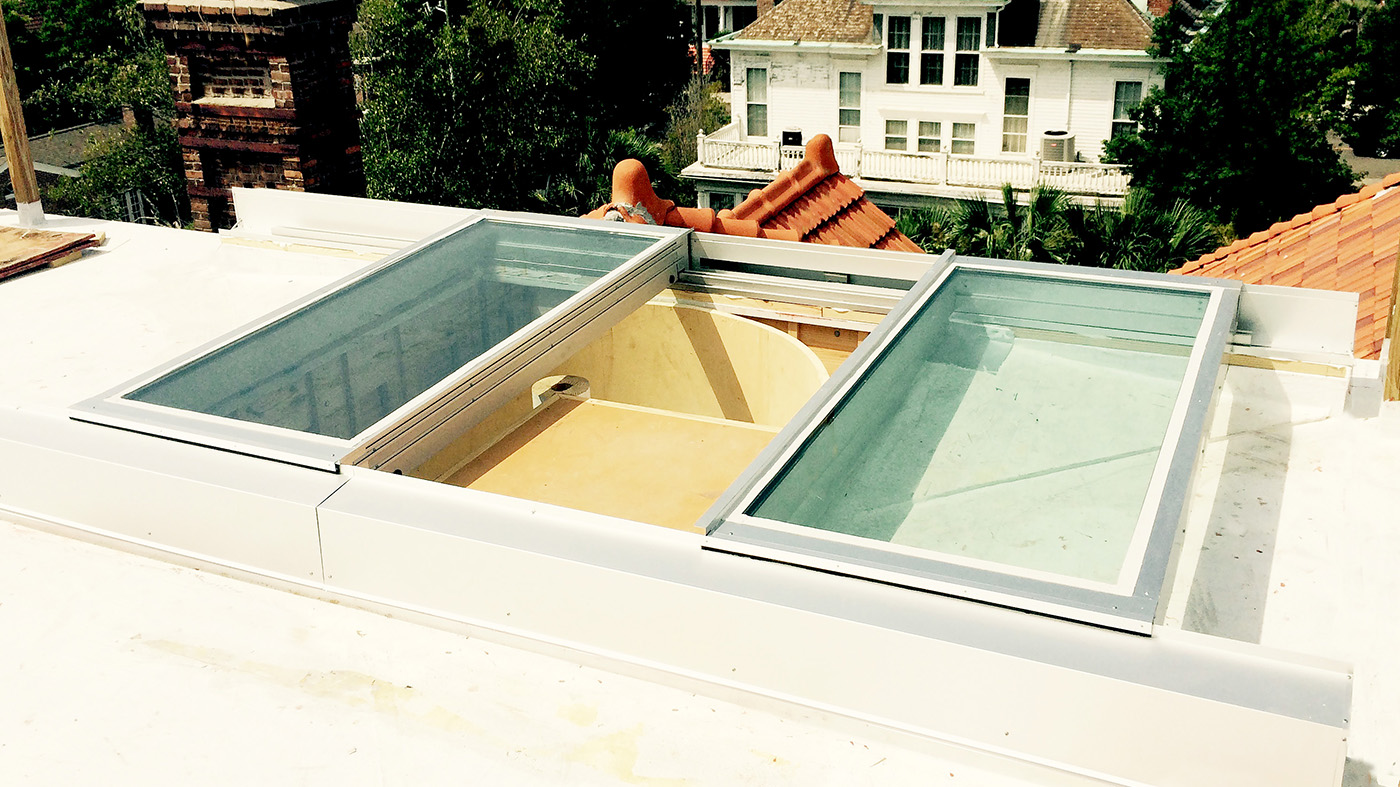 Bi-parting retractable skylight with roof access