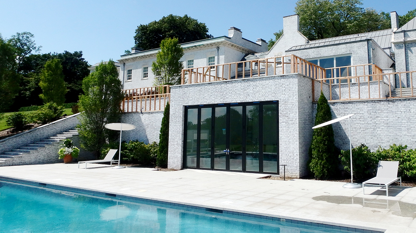 This folding glass wall opens up the pool house for an easy transition.