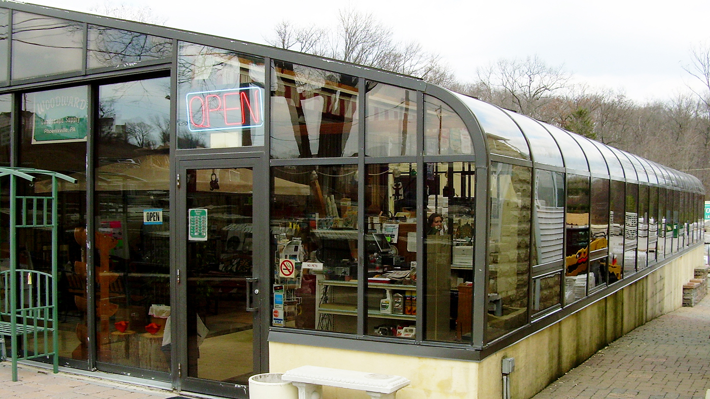 Curved eave lean-to greenhouse in this commercial end building supply store.