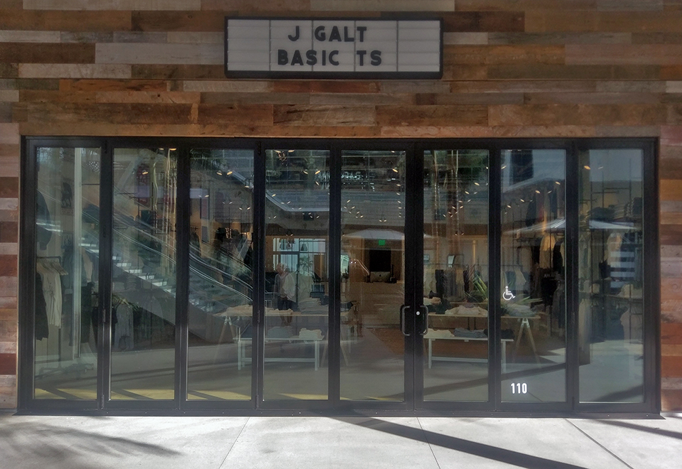 Folding Glass Wall on storefront to open up the store to the courtyard. This folding glass wall is made up of 8 panels, of which 2 are in system terrace doors.