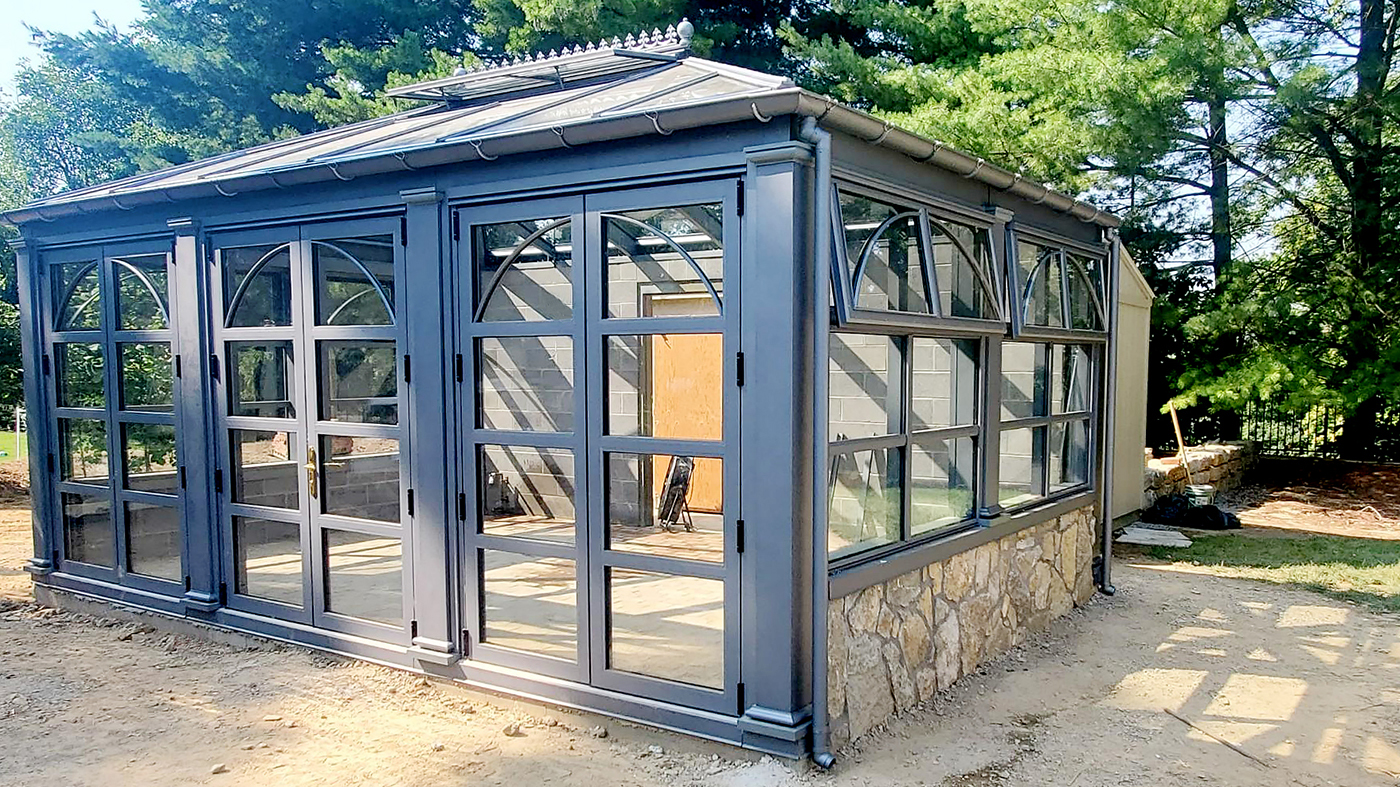 Straight eave double pitch hip end greenhouse with three sets of French doors with mullions and arched grids.