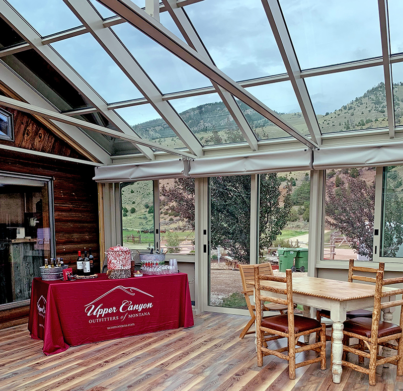 Straight eave double pitch sunroom with bifold door entryway to house