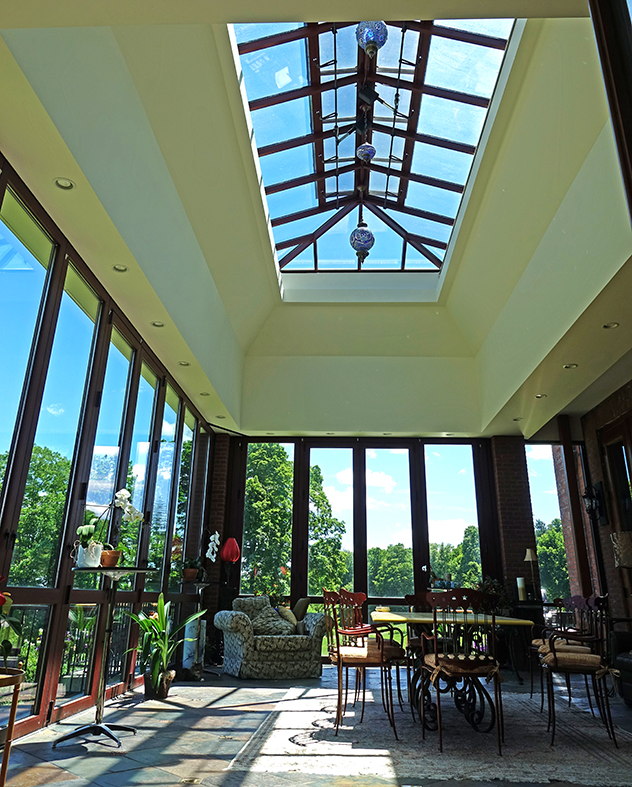 Sunroom with slide and stack doors, curtain wall and double pitch skylight.